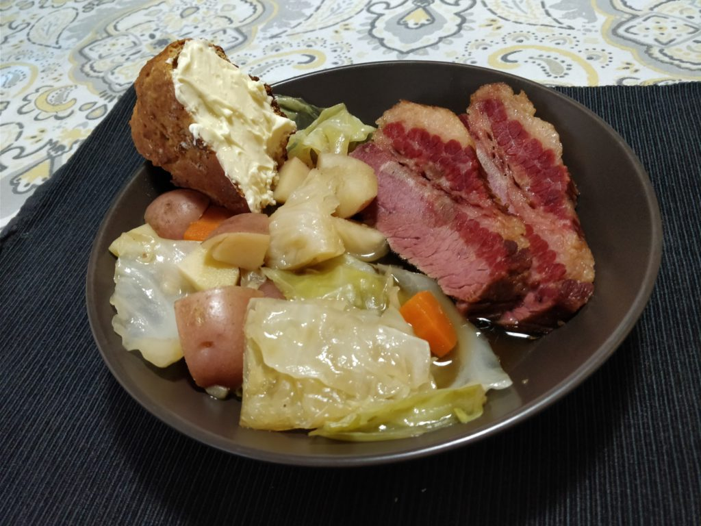 plate of corned beef, cabbage, potatoes, carrots, parsnip, and heavily-buttered soda bread