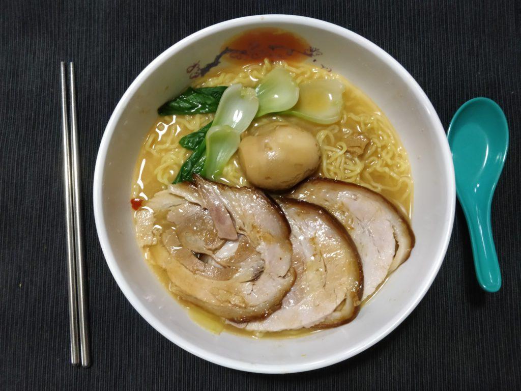 bowl of miso ramen featuring chashu pork, marinated bok choy (ohitashi), and a marinated egg