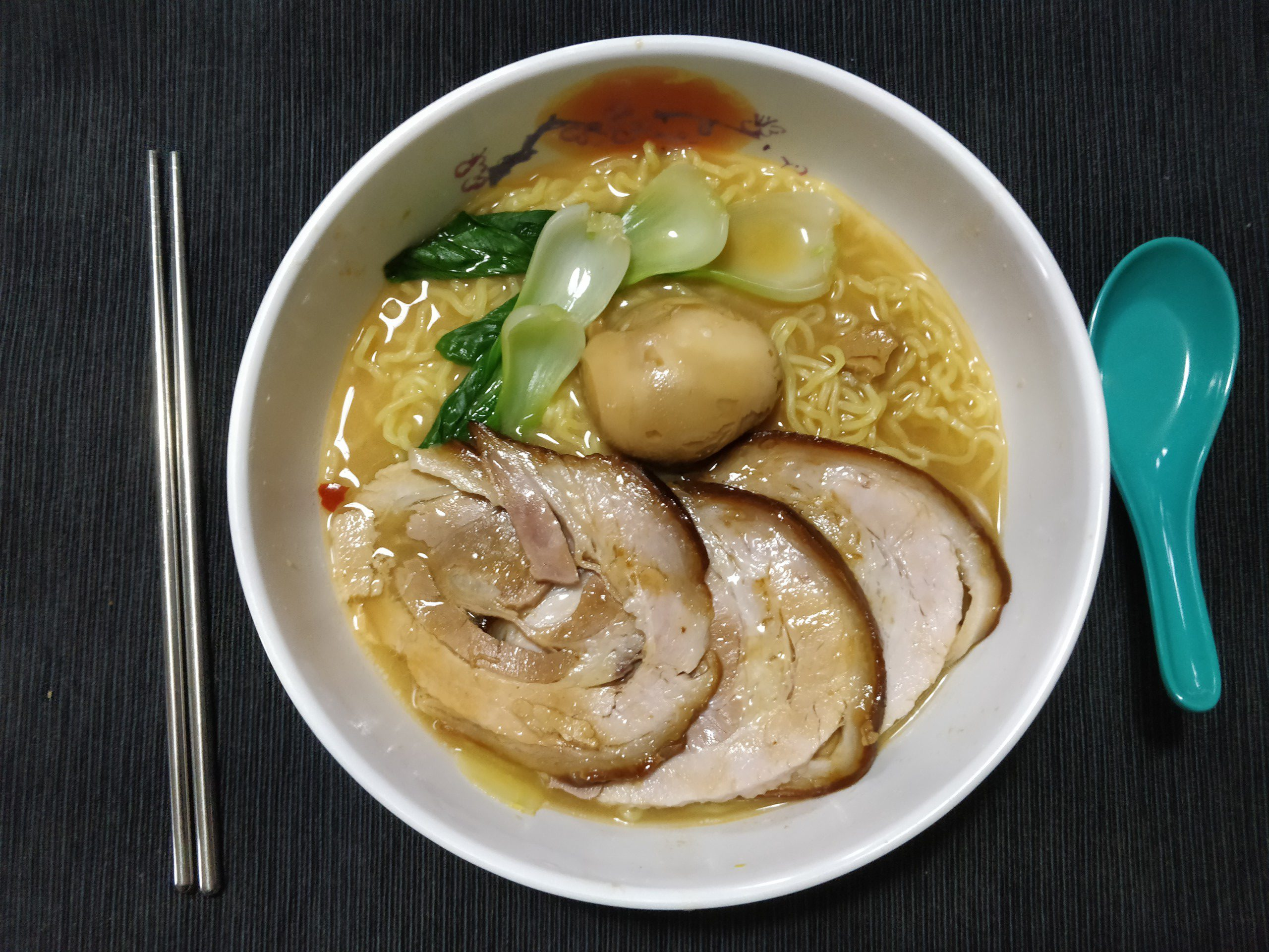 bowl of miso ramen featuring chashu pork, marinated bok choy (ohitashi), and a marinated egg