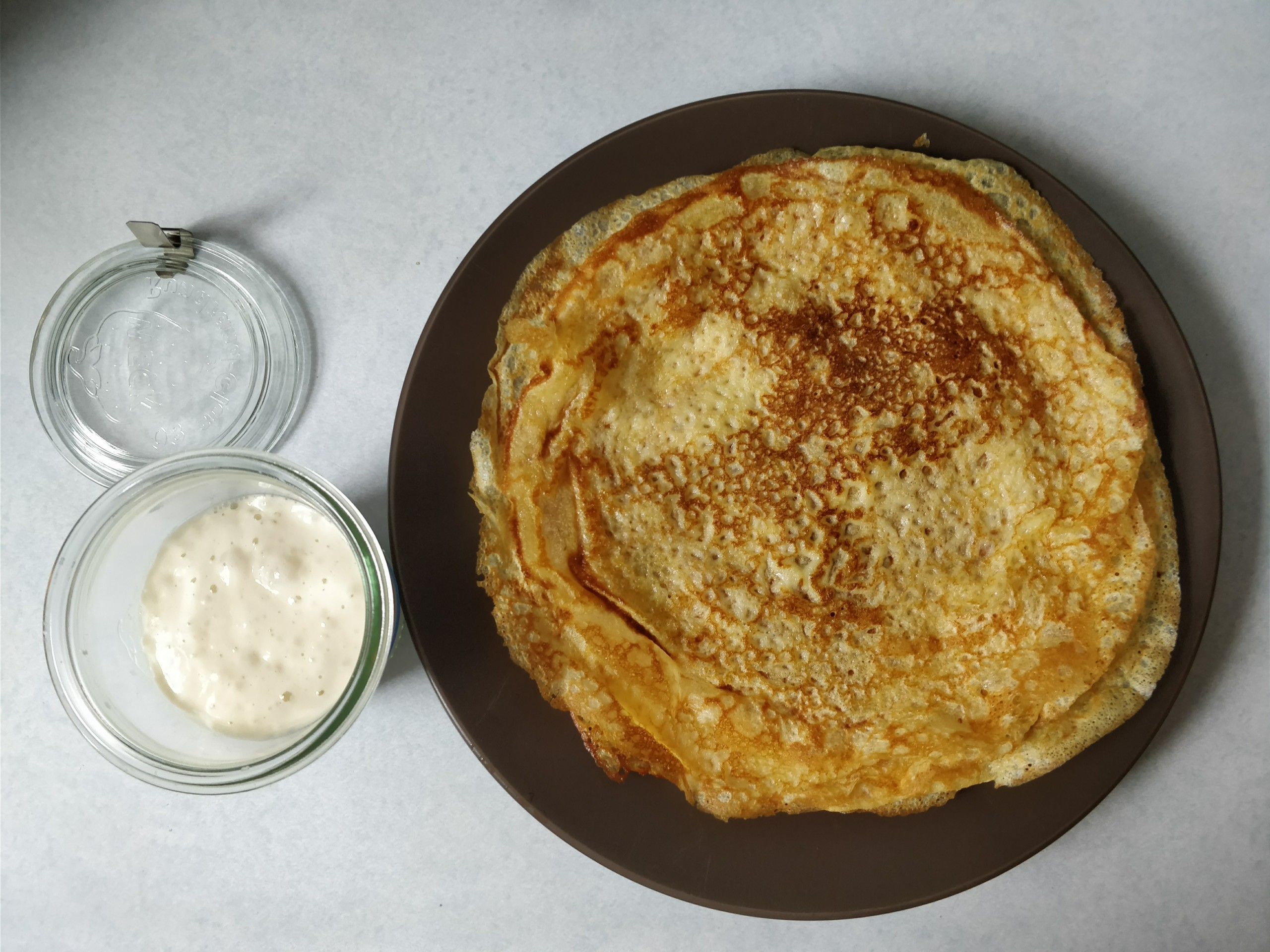 plate of sourdough crepes next to an open weck jar containing sourdough starter