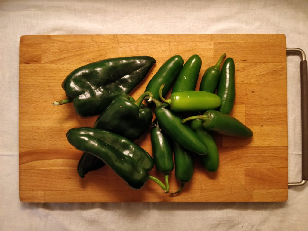 a pile of jalapenos and poblanos on a wooden cutting board