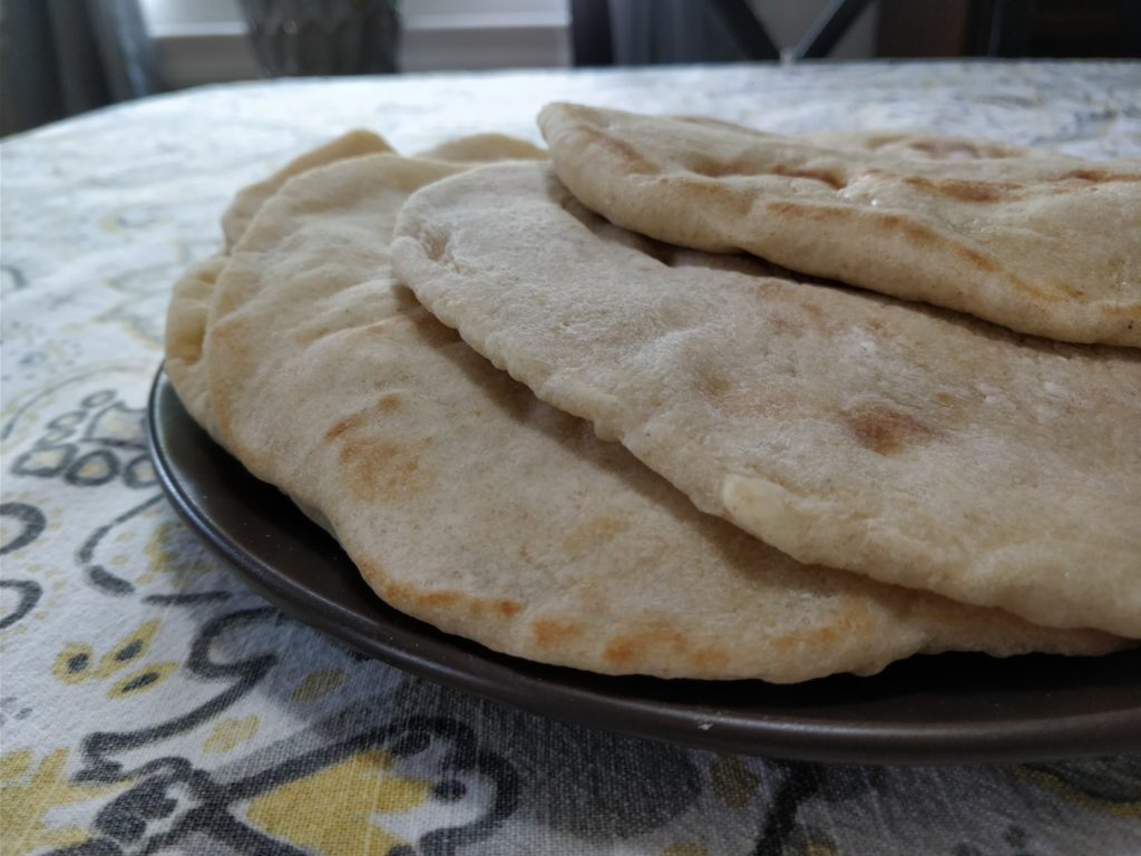 Photo of pita breads stacked on a plate.