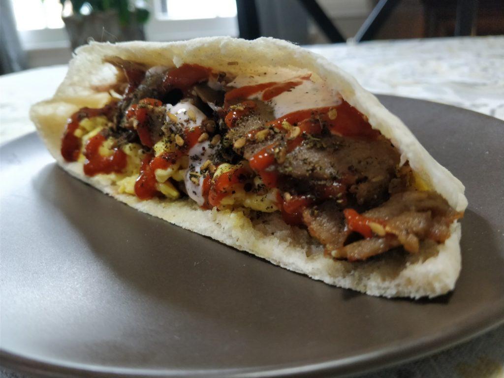 Photo of a pita stuffed with eggs, gyro meat, yogurt sauce, hot sauce, and zahtar.