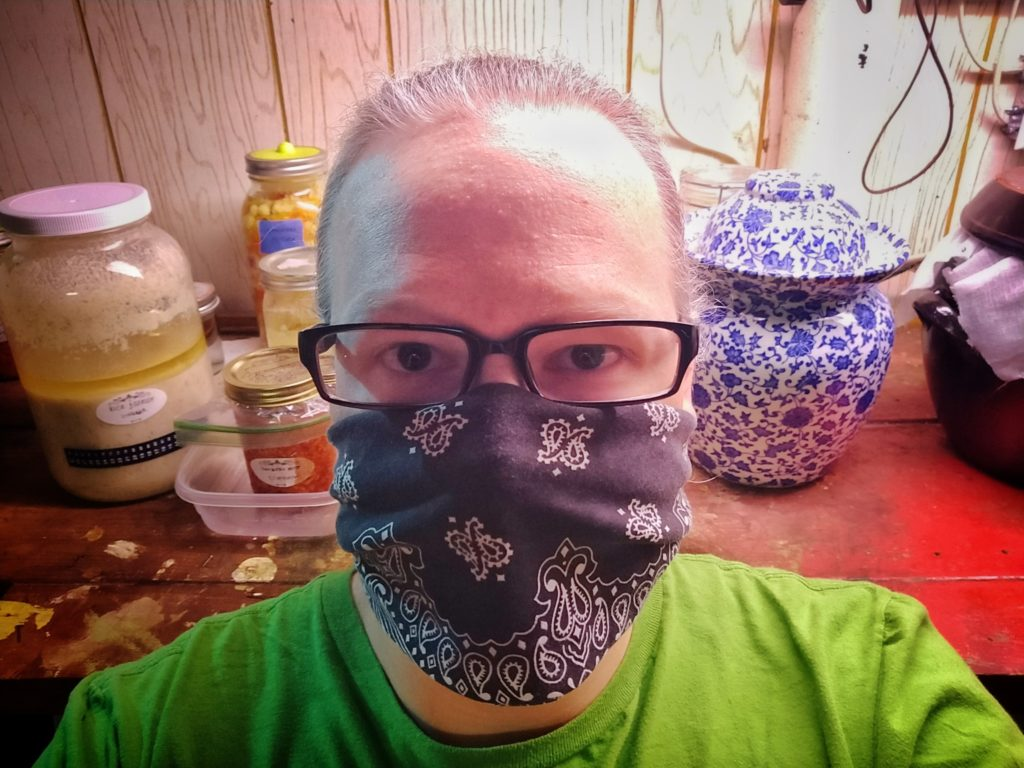 Cory with mask on in front of his shelf of fermentation jars