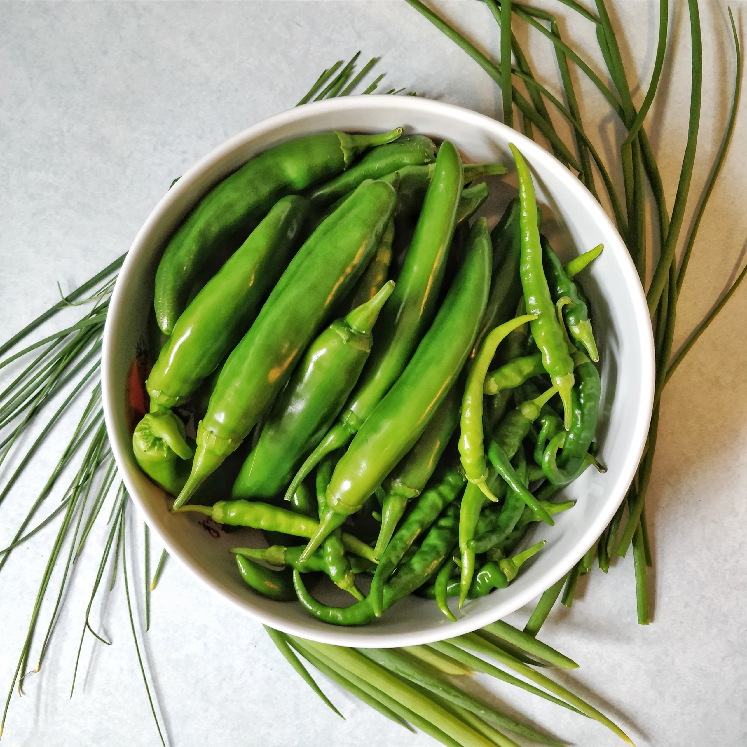 Bowl of green chilies surrounded by scallions
