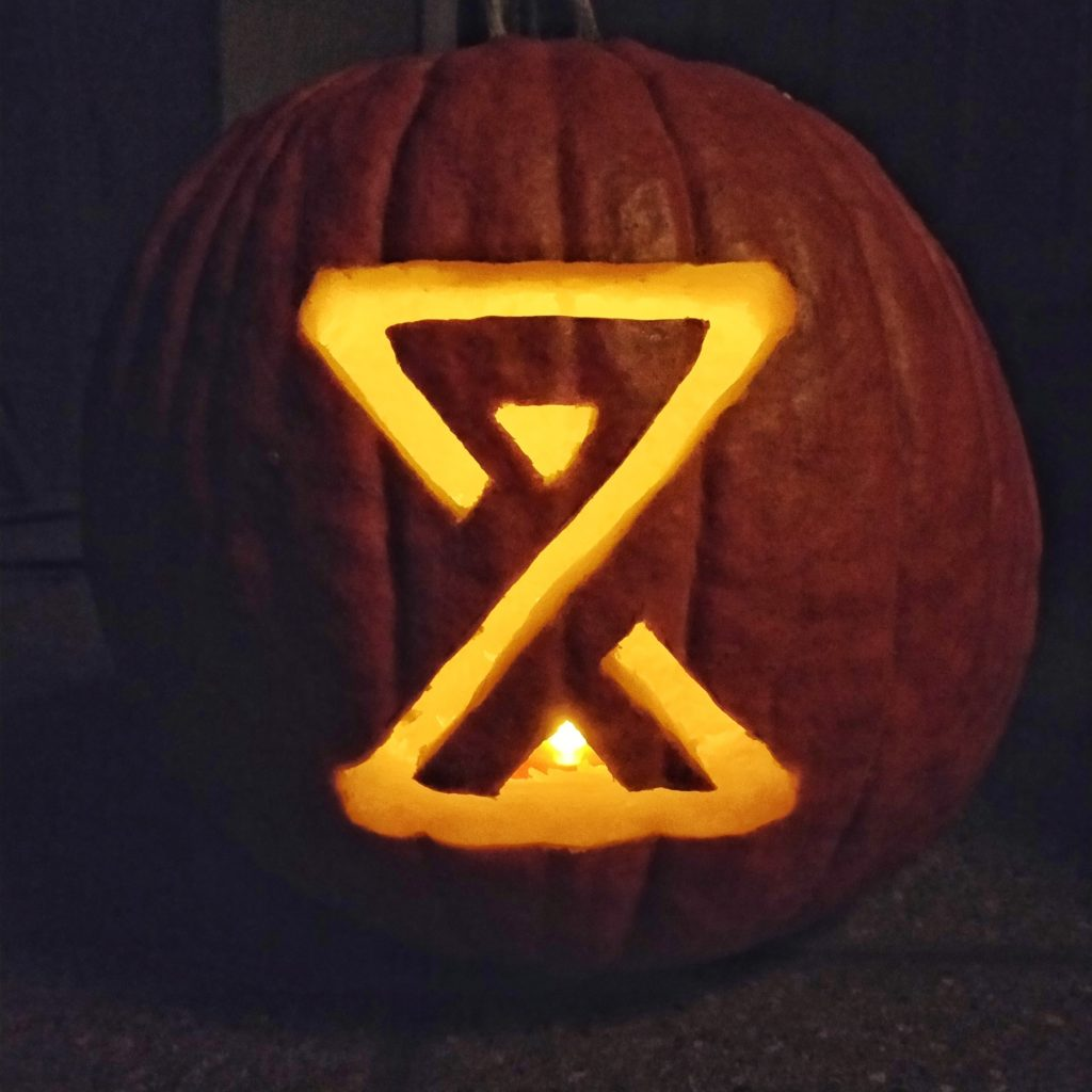 Pumpkin carved with the Crock of Time hourglass symbol, lit from within
