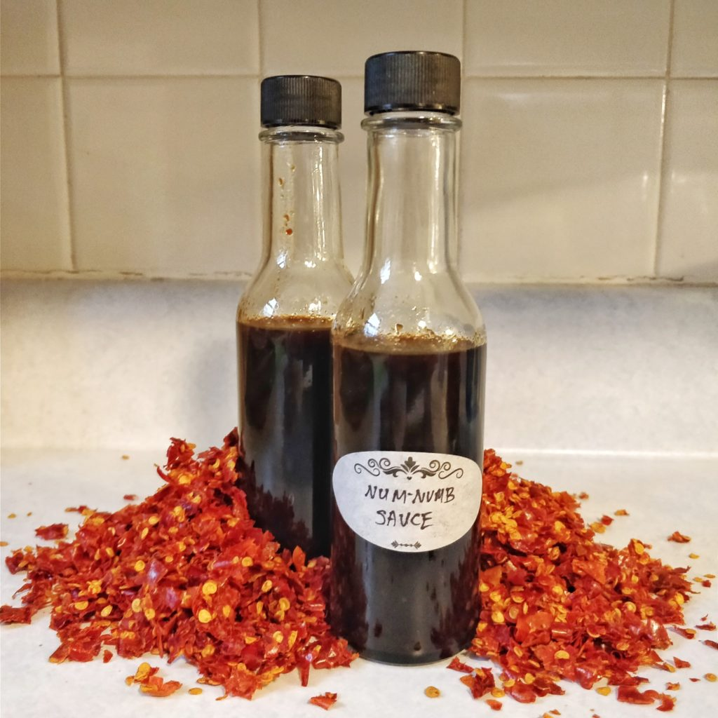 Two bottles of Num-Numb Sauce enveloped in a pile of chili flakes.