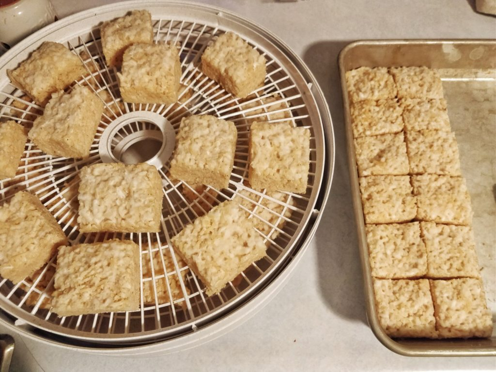 Cut squares of toasted koji rice placed into a small Nesco round dehydrator.